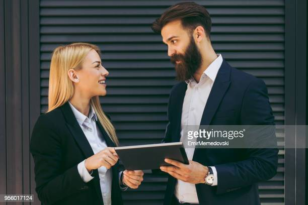 Male and female business people browsing on tablet computer