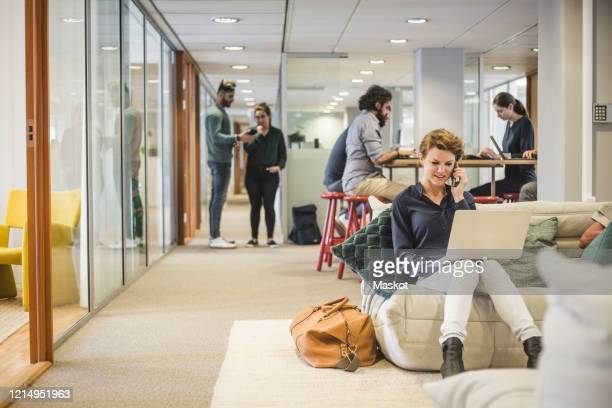 male and female business professionals working in creative office - coworking stock-fotos und bilder