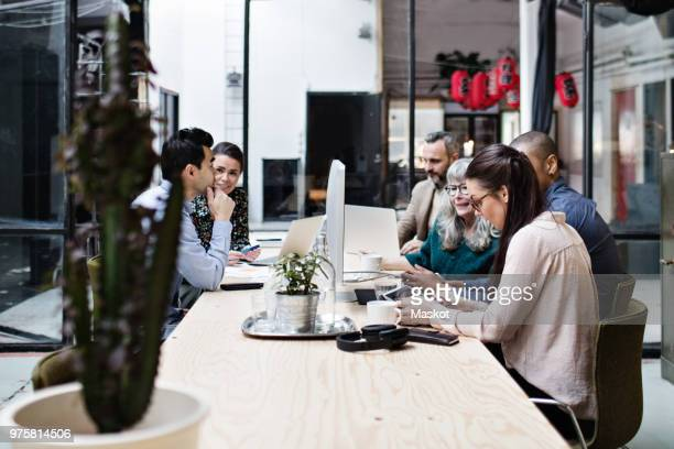 male and female business professionals working on technologies while discussing at table in meeting - business finance and industry stock pictures, royalty-free photos & images
