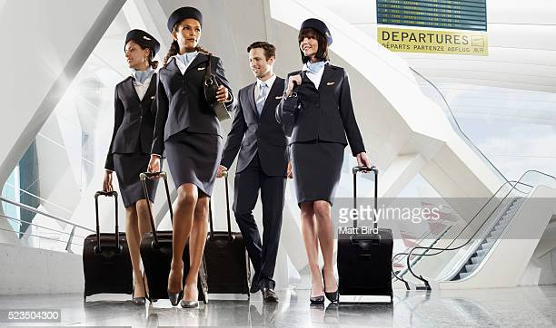 male and female cabin crew walking through large modern airport building - crew stock pictures, royalty-free photos & images