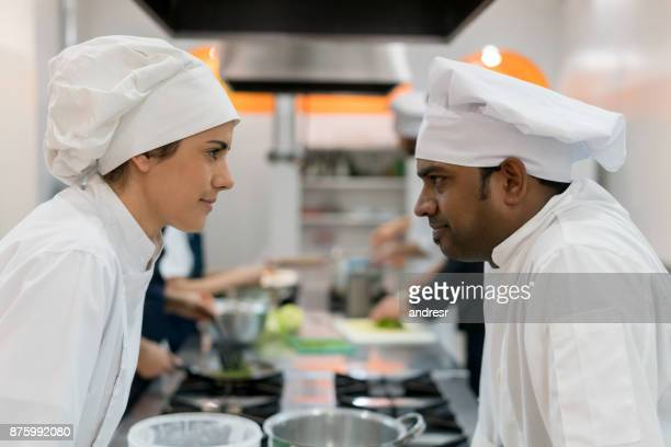 male and female chef looking at each other as rivals and challenging each other - rivalry stock pictures, royalty-free photos & images