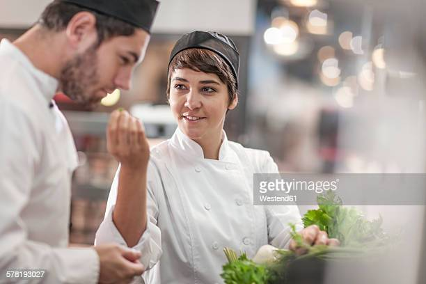 Male and female chef with fresh ingredients in restaurant kitchen