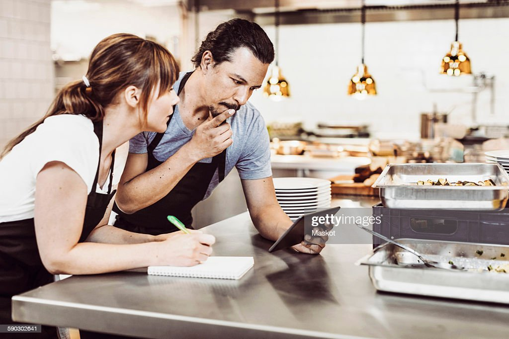 Male and female chefs using digital tablet while writing recipe at commercial kitchen counter : Stock Photo