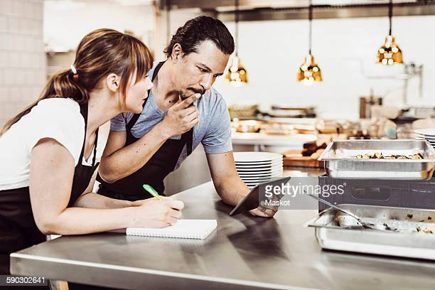 Male and female chefs using digital tablet while writing recipe at commercial kitchen counter