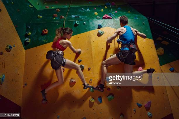 Male and female climbers purposeful climbs up the indoor climbing wall
