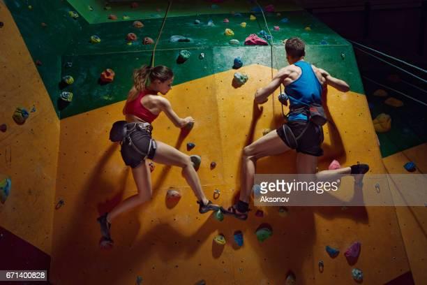 意図的な男性と女性の登山者が登って屋内上昇の壁