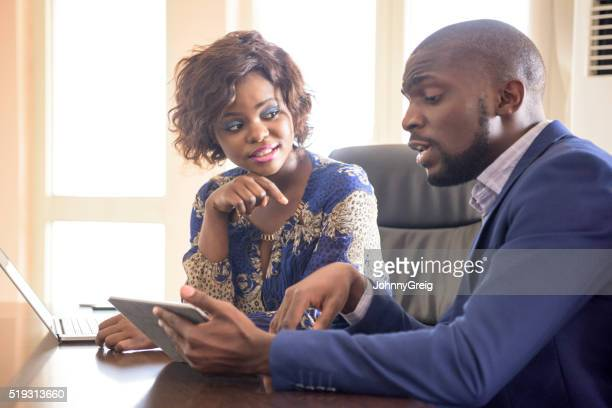 Male and female colleague using tablet in business meeting