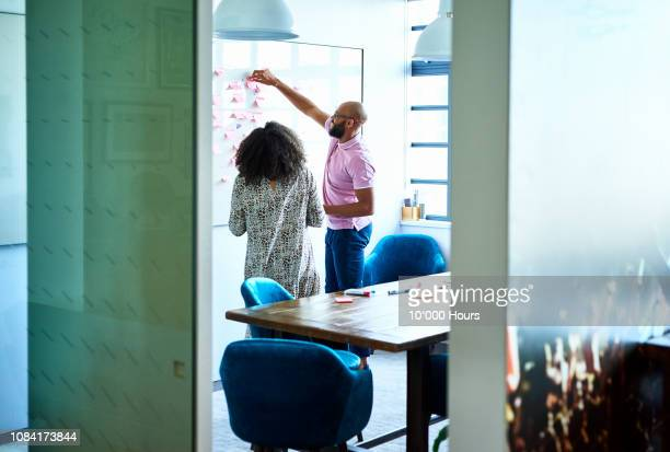 male and female colleagues brainstorming with adhesive notes on whiteboard - joining the dots stock pictures, royalty-free photos & images
