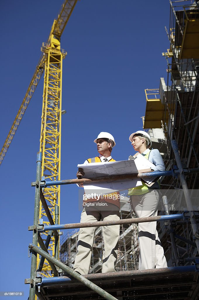 Male and Female Colleagues in Hard Hats Stand on a Platform in a Building Site Discussing a Blueprint : Stock Photo