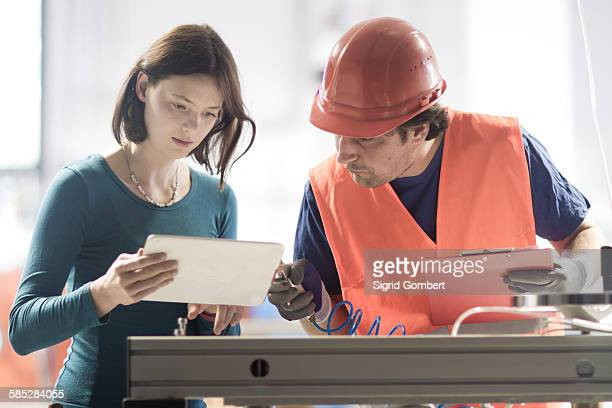 male and female colleagues in industrial occupation using digital tablet - sigrid gombert stock-fotos und bilder