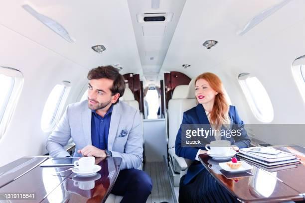 männliche und weibliche kollegen im privatjet - izusek stock-fotos und bilder