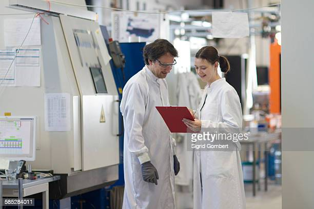 male and female colleagues wearing labcoats looking at clipboard smiling - sigrid gombert stock pictures, royalty-free photos & images