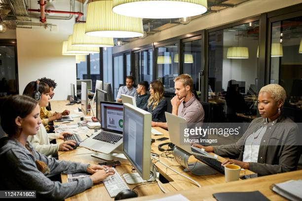 male and female colleagues working in office - online community stock pictures, royalty-free photos & images