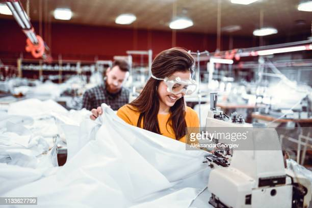 male and female colleagues working in textile industry - protective workwear stock pictures, royalty-free photos & images