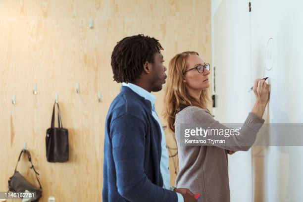 male and female colleagues writing business plan on whiteboard in office - business plan stock pictures, royalty-free photos & images