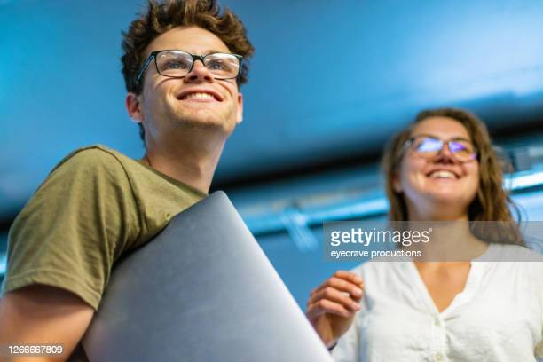 male and female college students wearing glasses holding laptop under arm looking out - eyecrave  stock pictures, royalty-free photos & images