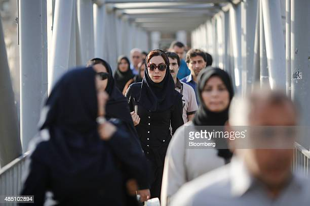 Male and female commuters cross a bridge on 7 E Tir Square in Tehran Iran on Saturday Aug 22 2015 Iran plans to raise oil production 'at any cost' to...