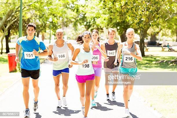 Male And Female Competitors Running Marathon