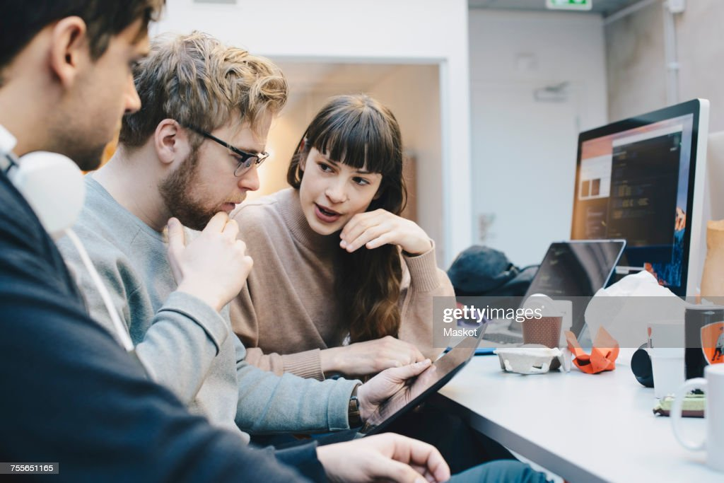 Male and female computer programmers discussing over digital tablet at desk in office : Stock Photo