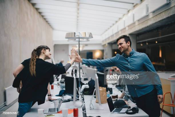 Male and female computer programmers giving high-five over desk in office