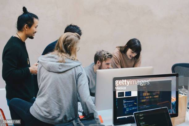 Male and female computer programmers using desktop PC in creative office