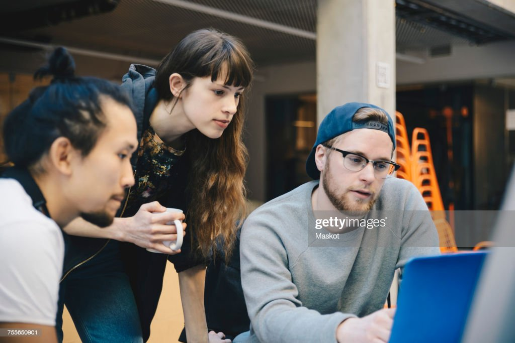 Male and female computer programmers using laptop at desk in office : Stock Photo