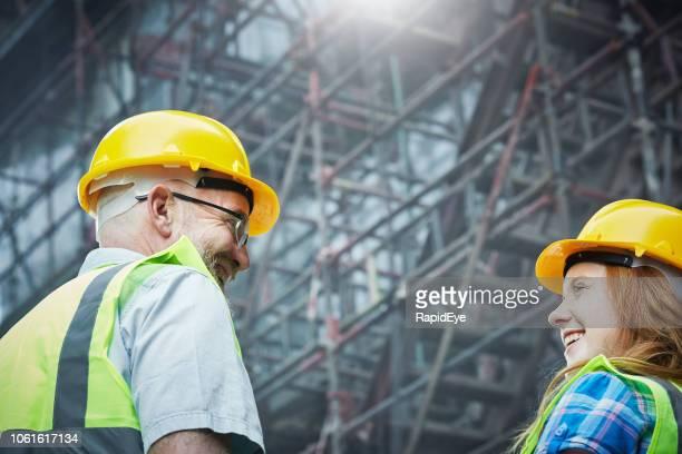 profesionales de la construcción de hombres y mujeres sonriendo por andamios - equidad de genero fotografías e imágenes de stock