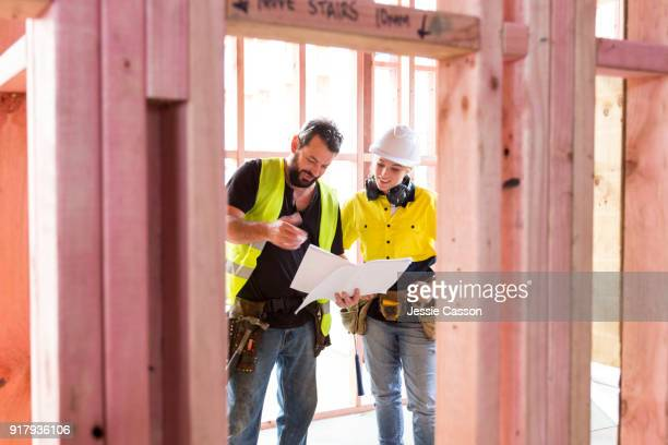 male and female construction workers discuss the building plans inside the building site - building contractor stock pictures, royalty-free photos & images