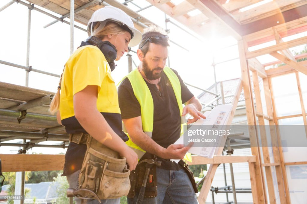 male and female construction workers discuss the building plans inside the building site : Stock Photo