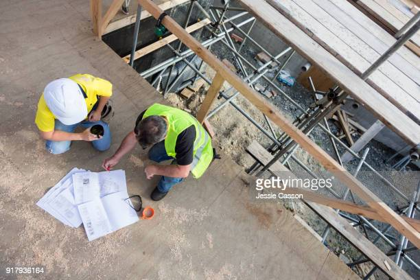 male and female construction workers discuss the building plans inside the building site