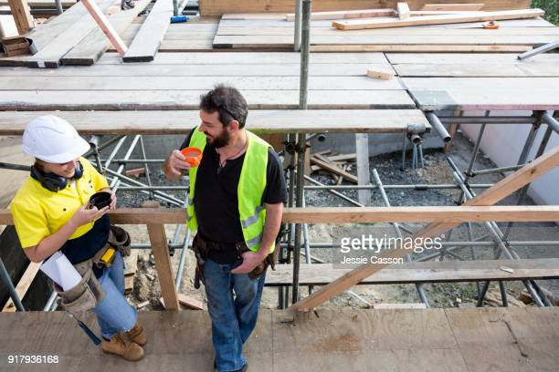 male and female construction workers have a break and cup of tea on the building site