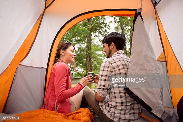 Male and female couple clinking coffee mugs in their tent