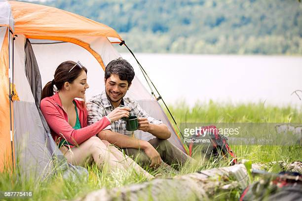 Male and female couple clinking coffee mugs while camping