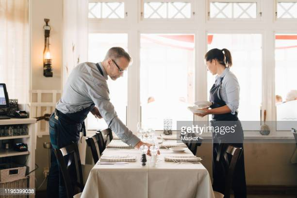 male and female coworkers arranging table in restaurant - arrangiare foto e immagini stock