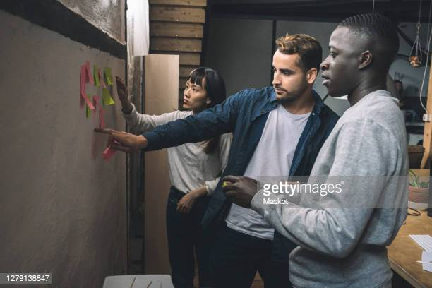 male and female coworkers sticking adhesive note on wall at workplace - programmer stock pictures, royalty-free photos & images