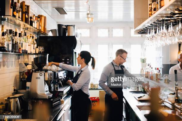 male and female coworkers working in kitchen at restaurant - waiter stock pictures, royalty-free photos & images