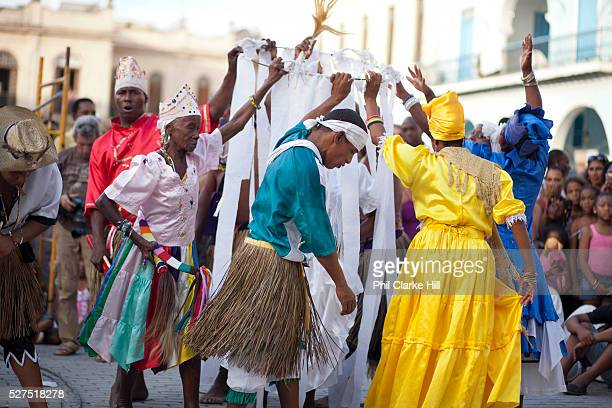 Male and female Cubans of African and mixed descendancy varying ages enacting a traditional ceremony wearing colourful costumes performance in Havana...
