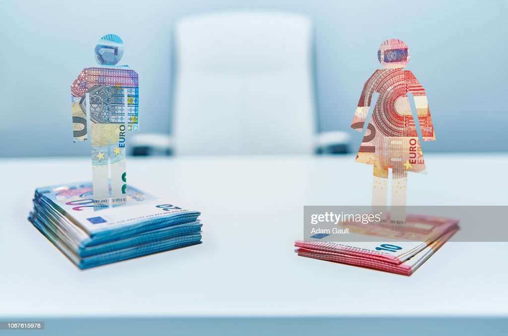 Male and Female Cut-out Figures on top of Bundles of EU Euro Notes : Stock Photo