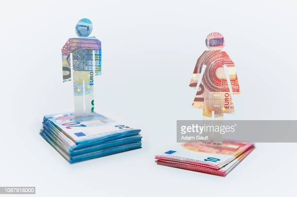 male and female cut-out figures on top of bundles of eu euro notes - wage gap stock pictures, royalty-free photos & images
