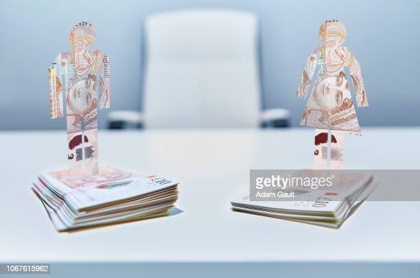 male and female cut-out figures on top of bundles of ten pound sterling notes - gender pay gap stock photos and pictures