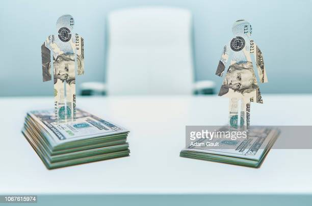 male and female cut-out figures on top of bundles of twenty usd united states dollar notes - wage gap stock pictures, royalty-free photos & images