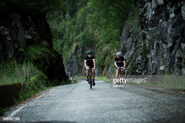 male and female cyclist driving down mountain road - wielrennen stockfoto's en -beelden