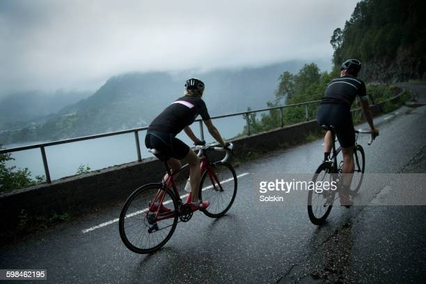 male and female cyclists on mountain road - road cycling stock pictures, royalty-free photos & images