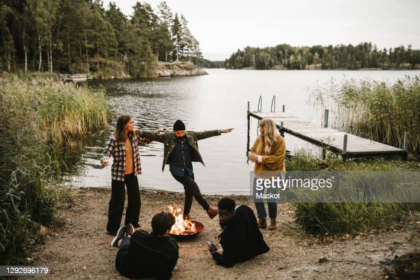 male and female dancing by fire pit while friends sitting near lake during social gathering - sweden stock pictures, royalty-free photos & images