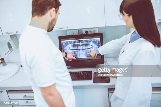 Male And Female Dentist Identifying Patient's Problem On Computer X-Ray