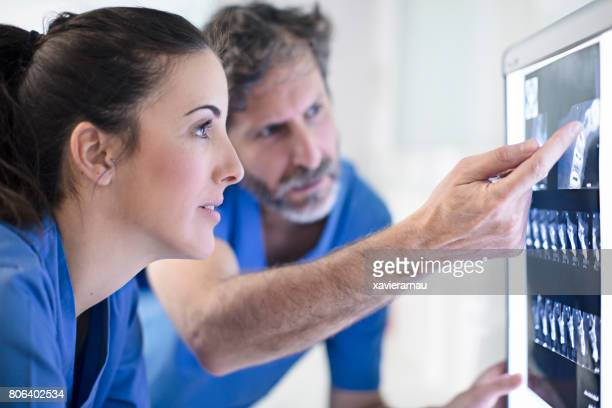 male and female dentists discussing x-ray image - dentist imagens e fotografias de stock