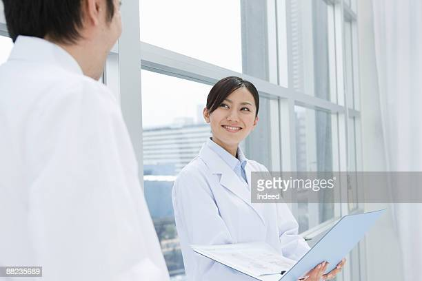 Male and female doctor smiling each other