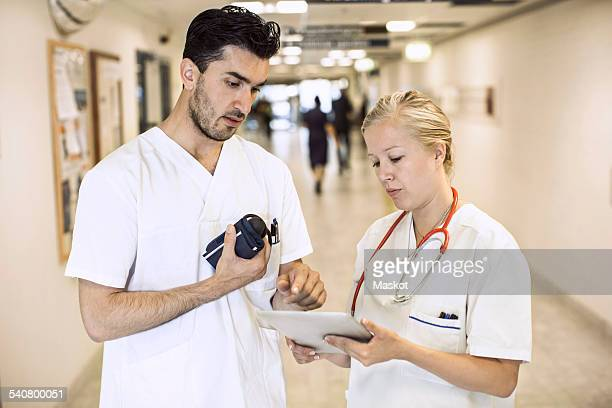 Male and female doctors discussing over digital tablet in hospital corridor