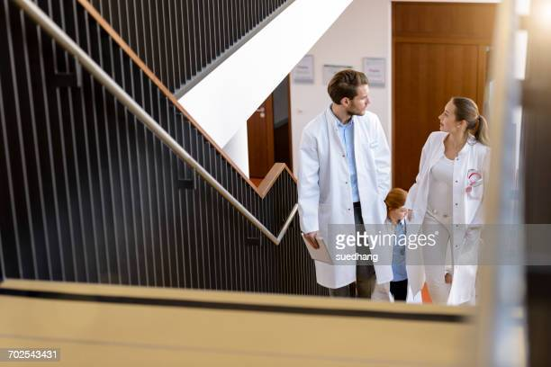 male and female doctors moving up hospital stairway, talking - ジュニアドクター ストックフォトと画像