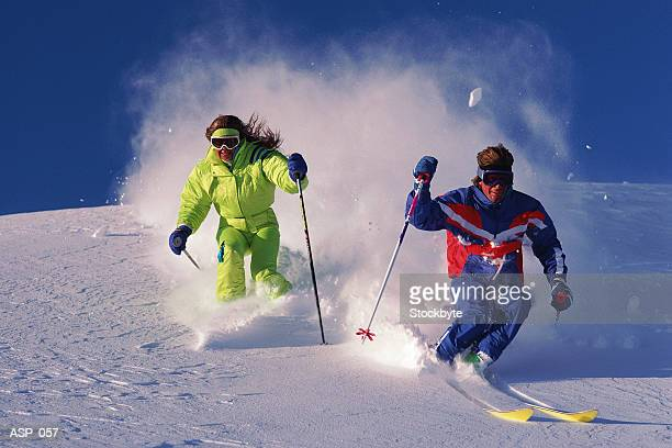Male and female downhill skiing